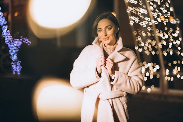 Jonge vrouw buiten de nachtstraat met lichten