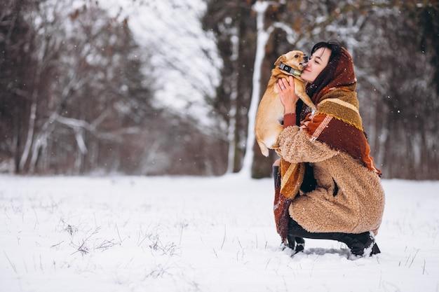 Jonge vrouw buiten het park met haar kleine hond in de winter