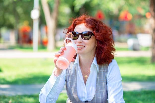 Jonge vrouw buiten in het park drinkt water uit een herbruikbare fles