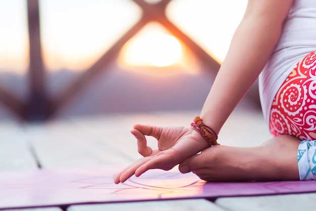 Jonge vrouw buiten mediteren op natuur zonsondergang close-up op handen doen yoga mudra
