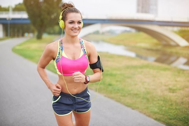 Jonge vrouw buiten uitoefenen. joggen boven de rivier in het park Gratis Foto