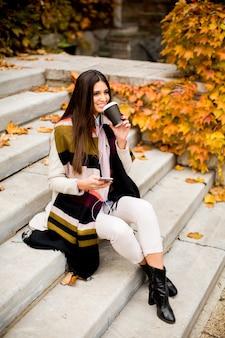Jonge vrouw buiten zitten, drinken koffie te gaan en een mobiele telefoon in de hand te houden