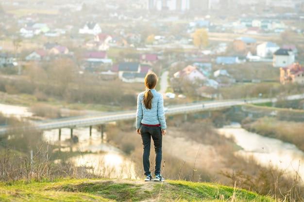 Jonge vrouw buitenshuis genieten van uitzicht op de stad.
