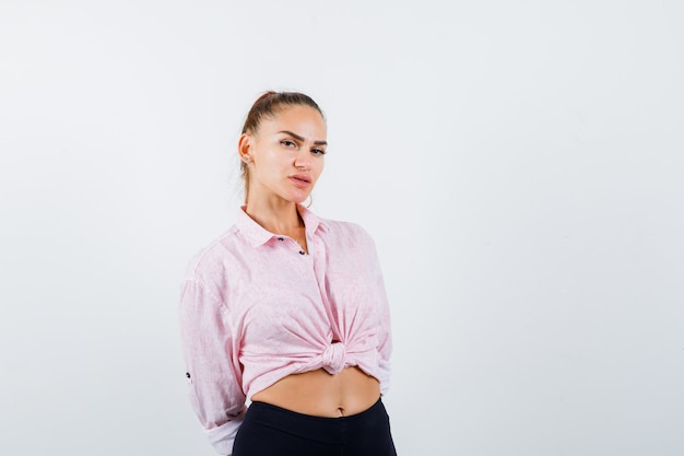 Jonge vrouw camera kijken terwijl hand in hand achter rug in casual shirt, broek en op zoek zelfverzekerd. vooraanzicht.