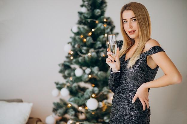 Jonge vrouw champagne drinken door kerstboom