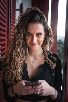 Jonge vrouw chatten met haar mobiele telefoon op het terras