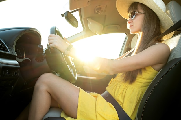 Jonge vrouw chauffeur in gele zomerjurk en strohoed autorijden.