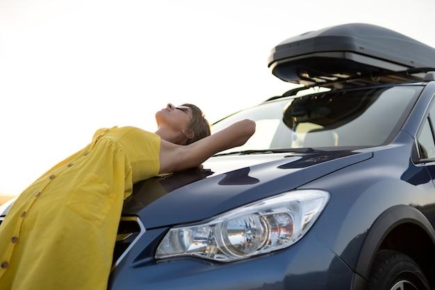 Jonge vrouw chauffeur rust in de buurt van haar auto in warme zomeravond.