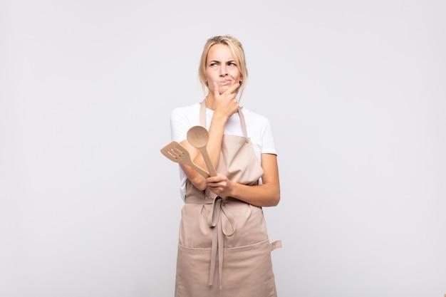 Jonge vrouw chef-kok denken, twijfelachtig en verward voelen, met verschillende opties, zich afvragend welke beslissing ze moeten nemen