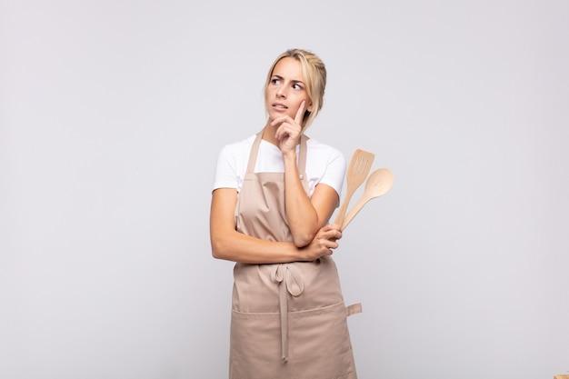Jonge vrouw chef-kok glimlachend gelukkig en dagdromen of twijfelen, op zoek naar de kant