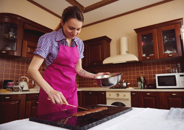 Jonge vrouw chocolatier cake schrapers houden in de buurt van gesmolten chocolade op marmeren oppervlak op het oppervlak van houten keuken
