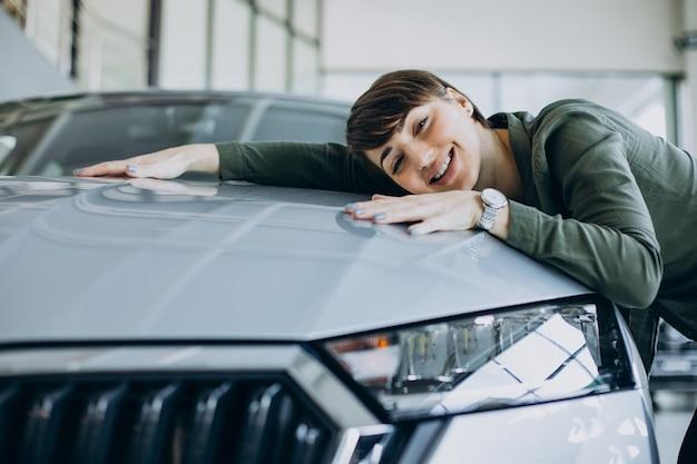 Jonge vrouw choosimng een auto in een autoshowroom