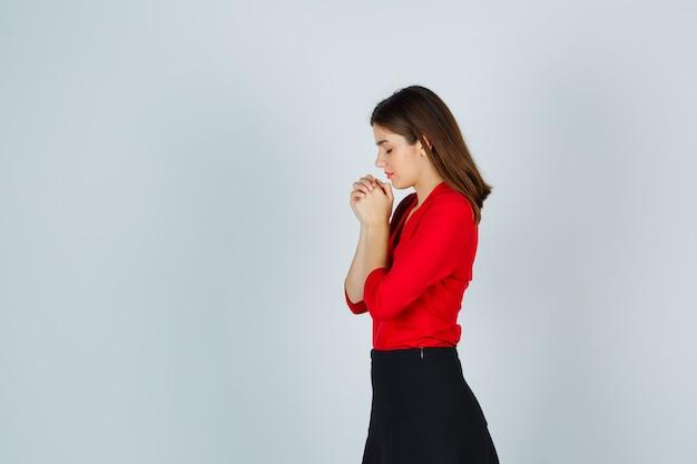 Jonge vrouw clasping handen in biddende positie in rode blouse