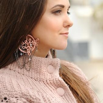 Jonge vrouw close-up portret, roze boho stijl dreamcatcher oorbellen