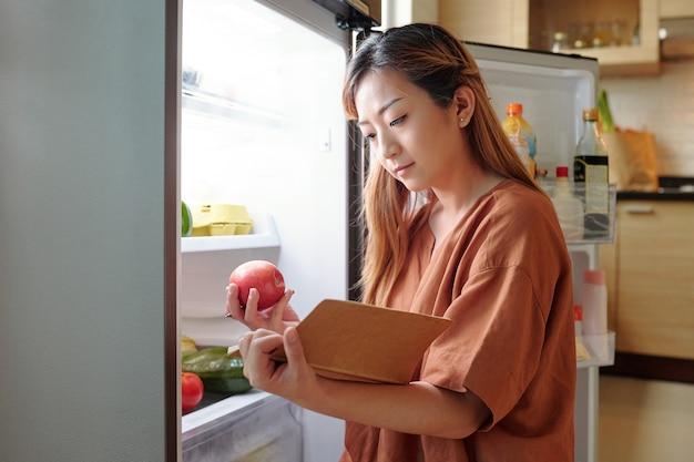 Jonge vrouw controleert of ze genoeg fruit in de koelkast heeft en maakt een boodschappenlijstje