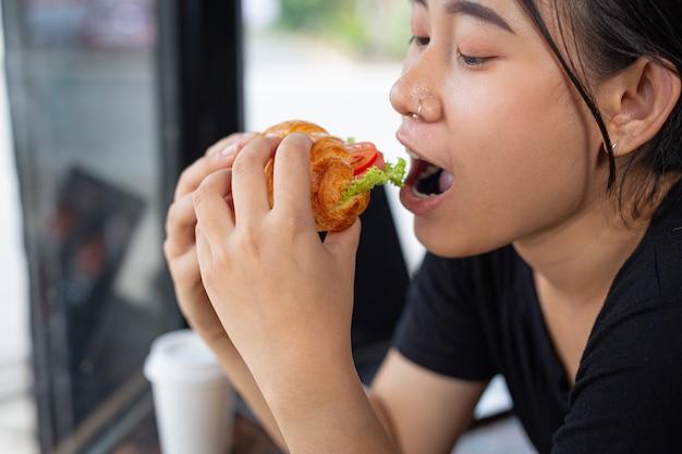 Jonge vrouw croissantsandwiches eten in kantoorruimte