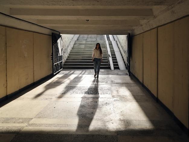 Jonge vrouw daalt af in een sombere onderdoorgang en twee schaduwen dalen achter haar neer