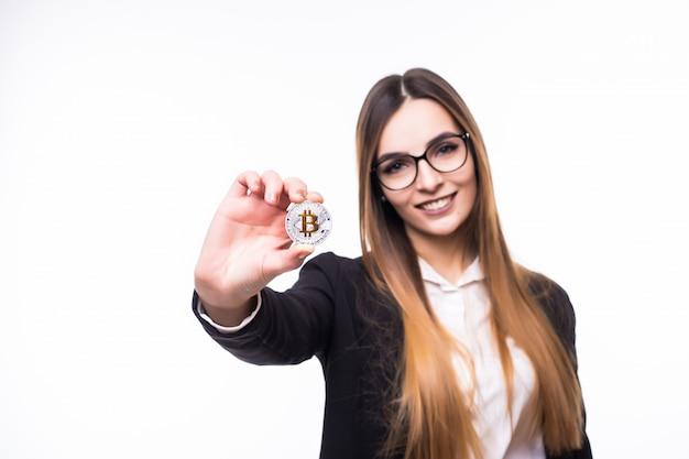 Jonge vrouw dame houdt bitcoin munt in haar handen op wit