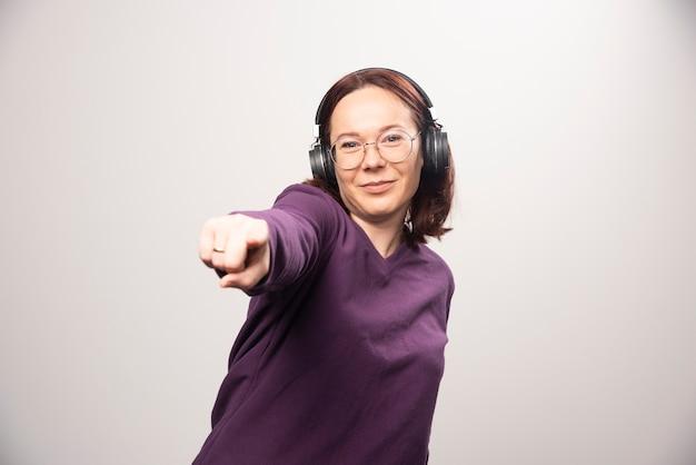 Jonge vrouw dansen en luisteren muziek in koptelefoon op een witte achtergrond. hoge kwaliteit foto
