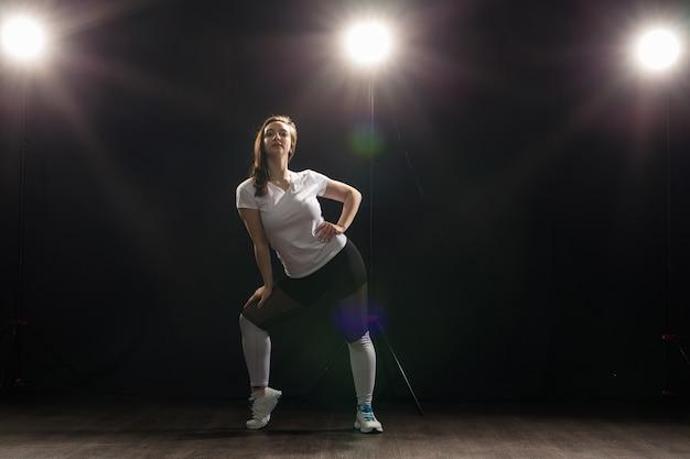 Jonge vrouw danser gymnastiek oefening pose op donkere achtergrond.
