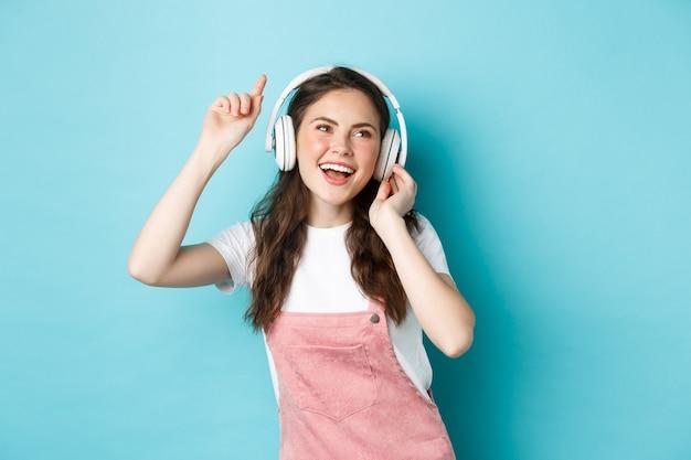 Jonge vrouw danst en luistert naar muziek in een koptelefoon, steekt hand op en lacht zorgeloos, geniet van haar favoriete liedje, staande over blauwe achtergrond
