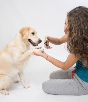 Jonge vrouw de nagels van de hond snijden met speciaal gereedschap