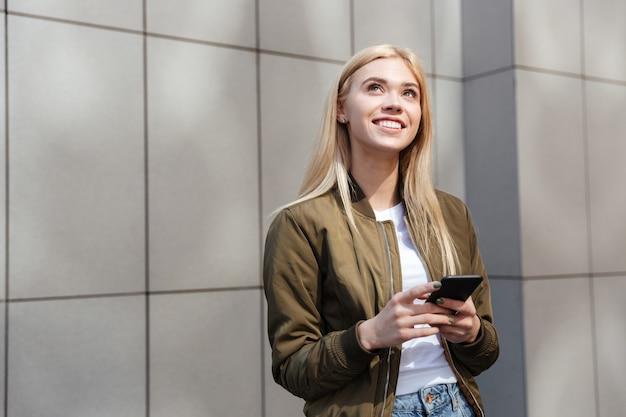 Jonge vrouw denken tijdens het gebruik van smartphone