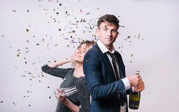 Jonge vrouw dichtbij man met fles drank tussen het werpen van confettien