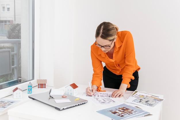 Jonge vrouw die aan blauwdruk aan bureau werkt