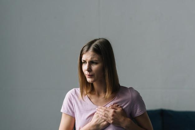 Jonge vrouw die aan borstpijn lijdt