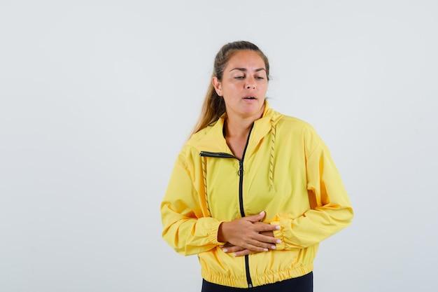 Jonge vrouw die aan buikpijn in gele regenjas lijdt en onrustig kijkt