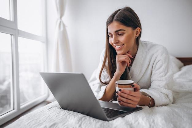 Jonge vrouw die aan computer in bed werkt