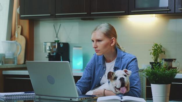 Jonge vrouw die aan de computer werkt en kleine hond op haar handen houdt