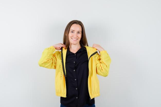 Jonge vrouw die aan de kraag van de jas trekt