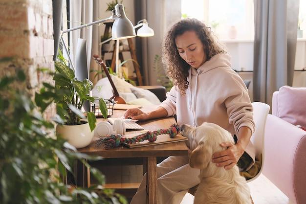 Jonge vrouw die aan de tafel met computer thuis werkt terwijl hond met haar wil spelen