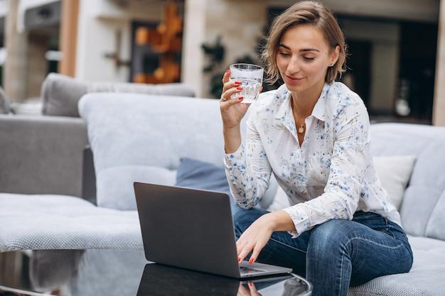 Jonge vrouw die aan een computer thuis werkt
