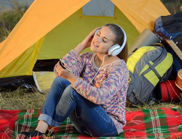 Jonge vrouw die aan een mp3 speler in een tent luistert