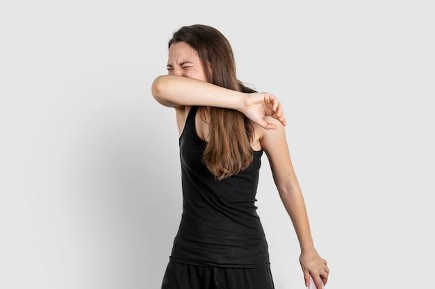 Jonge vrouw die aan elleboog niest. longontsteking of virusziekte. covid-19 pandemie