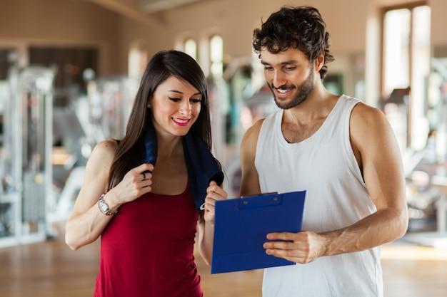 Jonge vrouw die aan haar geschiktheidstrainer spreekt in de gymnastiek aangezien zij het klembord in kaart brengen raadplegen