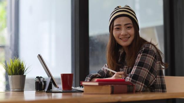 Jonge vrouw die aan haar project met tablet werkt tijdens het kijken en glimlachen naar de camera