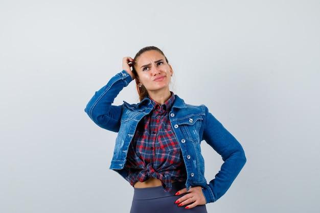 Jonge vrouw die aan het hoofd krabt terwijl ze de hand op de heup houdt in een geruit hemd, jas, broek en er attent uitziet, vooraanzicht.