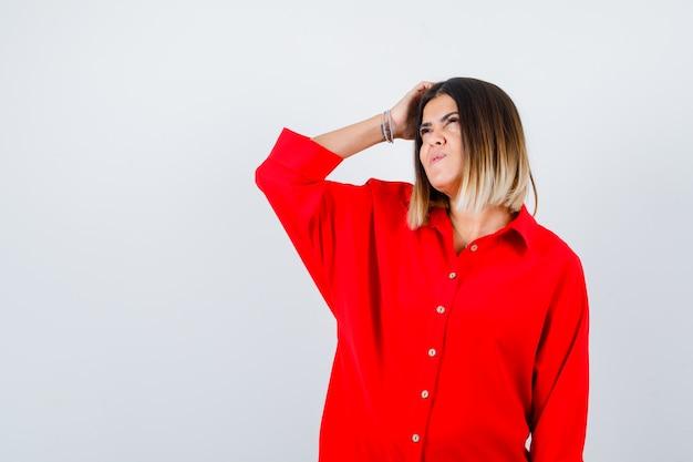 Jonge vrouw die aan het hoofd krabt terwijl ze opkijkt in een rood oversized shirt en er attent uitziet, vooraanzicht.