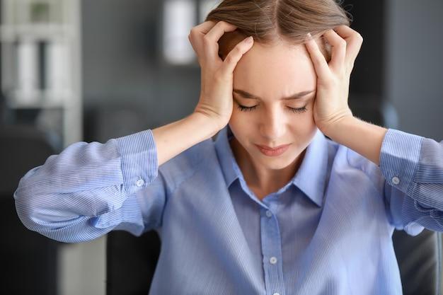 Jonge vrouw die aan hoofdpijn in bureau lijdt