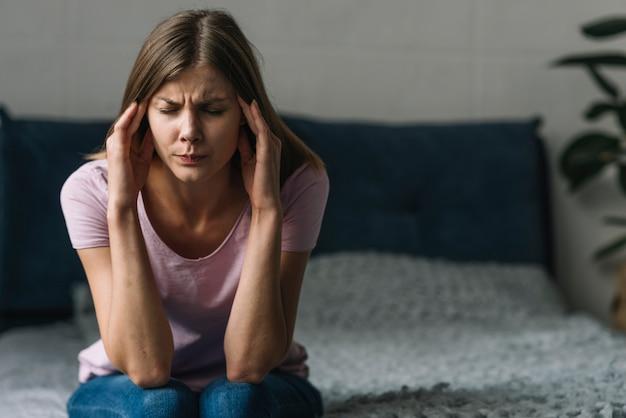 Jonge vrouw die aan hoofdpijnzitting op bed lijdt