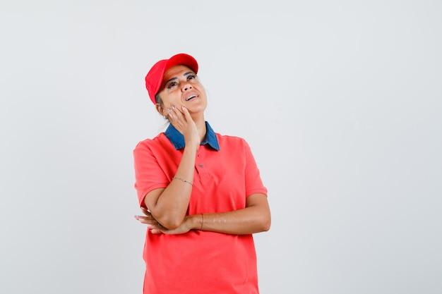 Jonge vrouw die aan iets denkt, wang op palm leunt terwijl hierboven in rood overhemd en glb kijkt en peinzend, vooraanzicht kijkt.