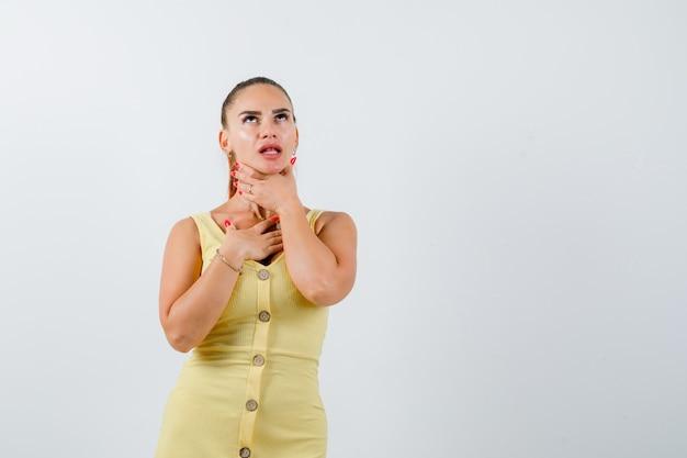 Jonge vrouw die aan keelpijn in gele kleding lijdt en ziek kijkt. vooraanzicht.
