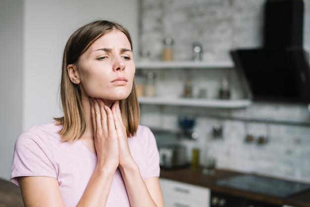 Jonge vrouw die aan keelpijn lijdt