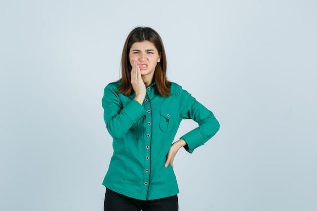 Jonge vrouw die aan kiespijn in groen overhemd lijdt en pijnlijk kijkt. vooraanzicht.
