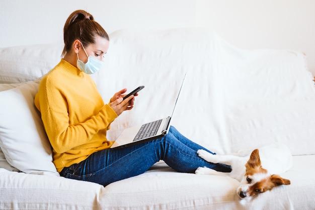 Jonge vrouw die aan laptop en mobiele telefoon, leuke kleine hond daarnaast werkt. zittend op de bank, met beschermend masker. blijf thuis concept tijdens coronavirus covid-2019