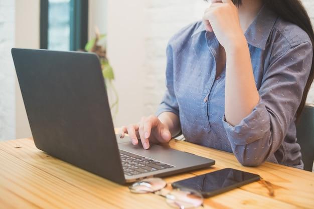 Jonge vrouw die aan laptop in de koffie werkt